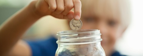 Boy Saving Coins In Money Jar
